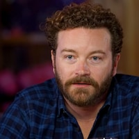 Danny Masterson, assis dans un bar, écoute une question du public.