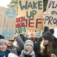 Un groupe de jeunes femmes et de jeunes hommes portant des tuques et brandissant des pancartes en faveur de l'environnement.