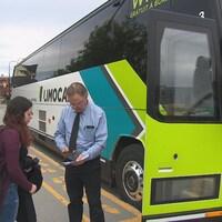 Une dame s'apprête à embarquer dans un autobus Limocar, à Sherbrooke. Le chauffeur valide son billet.