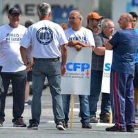 Des hommes portant des pancartes discutent en cercle.