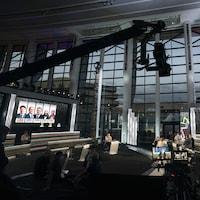 Un studio télé aménagé dans une immense salle. Sur un écran, les cinq chefs qui participent au débat.