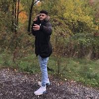 Yassin Dabeh porte un manteau d'hiver et pose devant une forêt.