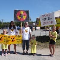 Deux femmes et des enfants tiennent des pancartes.