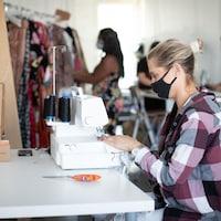 Une femme, de porfil, assise devant une machine à coudre.