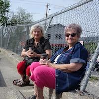 deux femmes avec un cafe assises dans un stationnement.