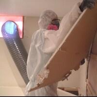 Un employé en habit de protection retire des panneaux de gypse d'un mur.