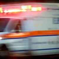 Une ambulance roule à pleine vitesse avec ses phares allumées en pleine nuit