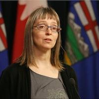 Deena Hinshaw parle devant les drapeaux canadiens et albertains de la salle des médias de l'Assemblée législative.