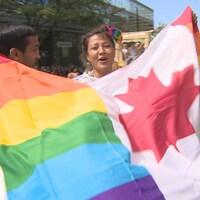 Une femme brandit le drapeau du Canada orné des couluers de la fierté gaie.