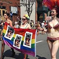 Trois femmes en bikini marchent avec une bannière aux couleurs de la fierté gaie. (Archives)