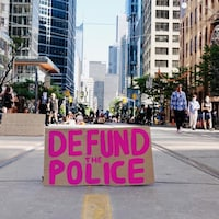 Un panneau « Defund the police » au milieu de la rue Bay, occupée par des manifestants assis.