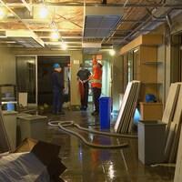 Un corridor avec des dégâts apparents et des travailleurs.