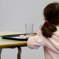 Une enfant qui fréquente une école primaire de l'Outaouais  devant un plateau de nourriture vide.