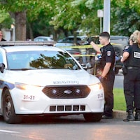 Des policiers établissent un périmètre de sécurité dans la rue.