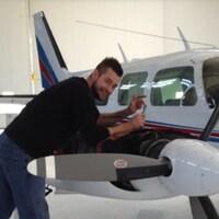 Un homme répare un avion de petite taille.