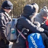 Des demandeurs d'asile, en compagnie d'un agent, à la frontière entre le Canada et les États-Unis en mars dernier
