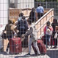 Un groupe de demandeurs d'asile arrive, valises à la main, aux installations d'hébergement temporaire au poste frontière à Saint-Bernard-de-Lacolle, Québec, le mercredi 9 mai 2018.