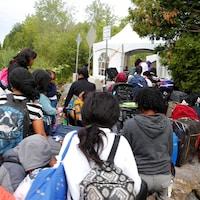 Une file de demandeurs d'asile attendent de franchir un point de contrôle installé au bout du chemin Roxham, à Saint-Bernard-de-Lacolle.