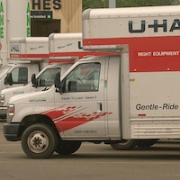 Trois camions de déménagement de type U-Haul.