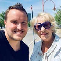 Photo de Derrek et Denise qui prennent un selfie dehors dans la rue.