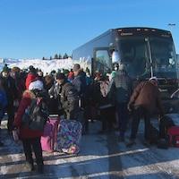 L'embarquement des athlètes dans un stationnement. On voit des gens attroupés autour d'un autobus avec des bagages.