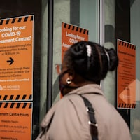 Une femme regarde les enseignes sur le dépistage de la COVID-19 à l'entrée d'un hôpital de Toronto.