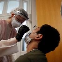 Une infirmière en combinaison de sécurité avec masque, charlotte et gants fait un test de dépistage de la COVID-19 à un homme.