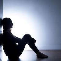 Une jeune fille assise au sol et adossée à un mur, dans l'obscurité.