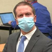 Derek Chauvin porte un masque bleu et un habit, il a l'air inquiet.