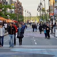 Des gens marchent sur une rue piétonne.