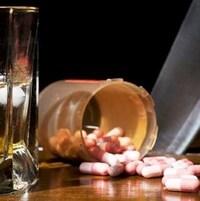 Un verre d'alcool et une bouteille de comprimés sur un bar
