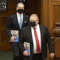 Deux hommes portant un masque noir entrent dans une salle.
