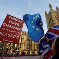 « Les choses ont changé. Il est temps de réévaluer », peut-on lire sur une pancarte installée devant le Parlement britannique, tout près d'une femme brandissant des drapeaux du Royaume-Uni et de l'Union européenne.