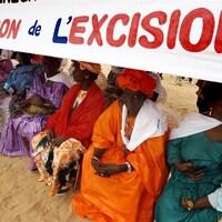 Des femmes en habits traditionnels tenant une banderole sur laquelle on peut lire « Pour l'abandon de l'excision ».