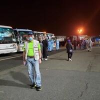 Des Canadiens parlent ou marchent devant une série d'autobus stationnées les uns à côté des autres.