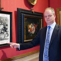 L'homme pointe du doigt une copie de tableau où il est marqué volé en plusieurs langues.