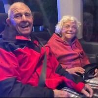 Un couple de personnes âgées dans une voiture, tout sourire.