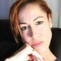 Un auto-portrait d'une femme avec les cheveux et les yeux bruns dans son salon.