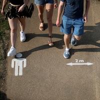 Des pictogrammes peints sur le ciment à Londres le 11 avril 2020 indiquent qu'il est recommandé de garder deux mètres de distance avec la personne la plus proche.