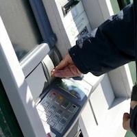 Un client à une distributrice de billets bancaires.