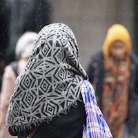 Une femme portant un voile marche sous une fine neige, à Montréal.