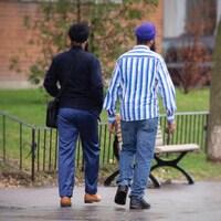 Deux hommes portant des turbans marchent sur un trottoir.
