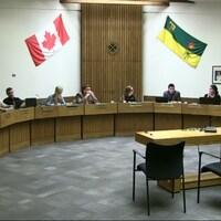 Les neuf des dix conseillers scolaires des divisions des écoles publiques de Regina assis lors de l'une de leurs assemblées.