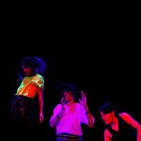 Deux danseuses et un danseur en performance dans le noir.
