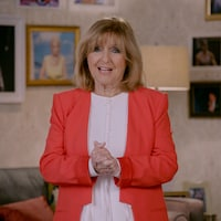 La femme croise les mains et parle à la caméra.
