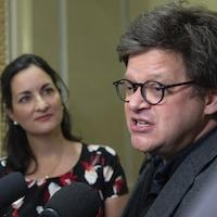 Un homme et une femme répondent aux questions de journalistes.