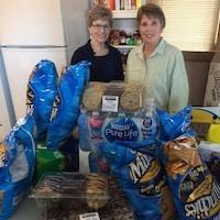 Diane Aminot et Suzanne Tétreault souriantes devant les dons alimentaires déposés sur une table.