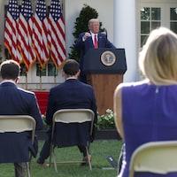 Devant des drapeaux américains, le président Trump, le bras levé, s'adresse aux journalistes, qu'on voit de dos.