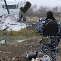 Un milicien prorusse, de dos, observe l'opération d'enlèvement des débris de l'appareil.