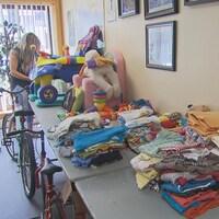 Des jouets et des vêtements pour enfants sont rassemblés sur une table.